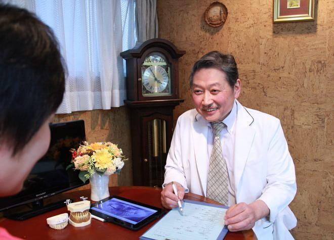 原田デンタルオフィス 原宿 患者に治療説明をする医院長の写真