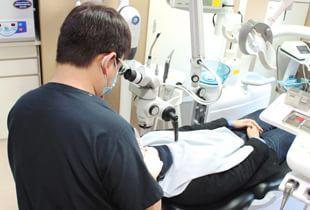 カラサワ歯科クリニック 新宿駅 治療を行う歯科医師の写真